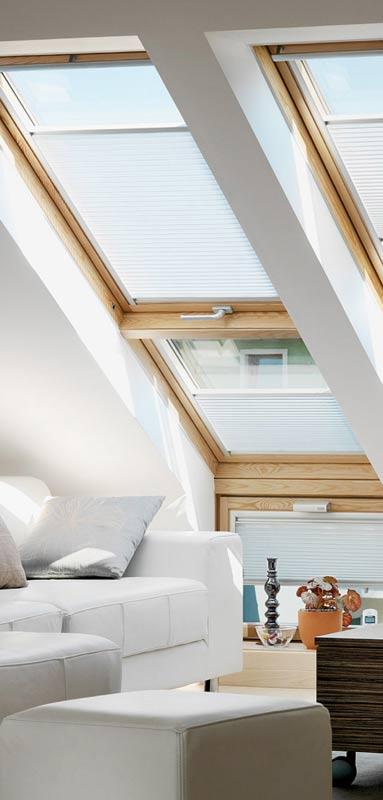 Innenraumszene mit VELUX GPL Klapp-Schwingfenstern, Erweiterung LICHTBAND und Fassadenanschluss-Fenstern in Holz Kiefer natur