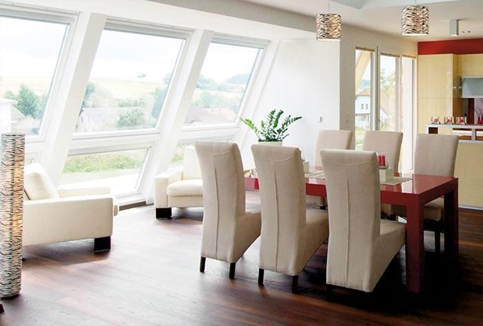 Bodentiefer VELUX GGU Lichtband-Drilling in einem modernen Wohnzimmer mit Essbereich in beige-rot.