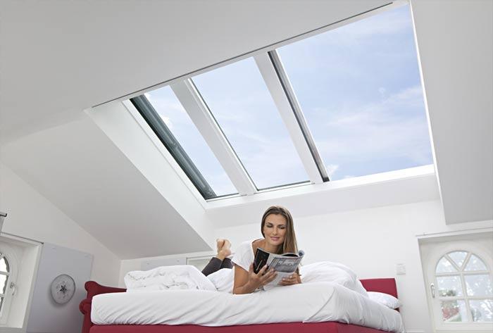 Das riesige Panorama-Dachfenster Azuro von Roto über einem großen Bett in weinrot und weiß.